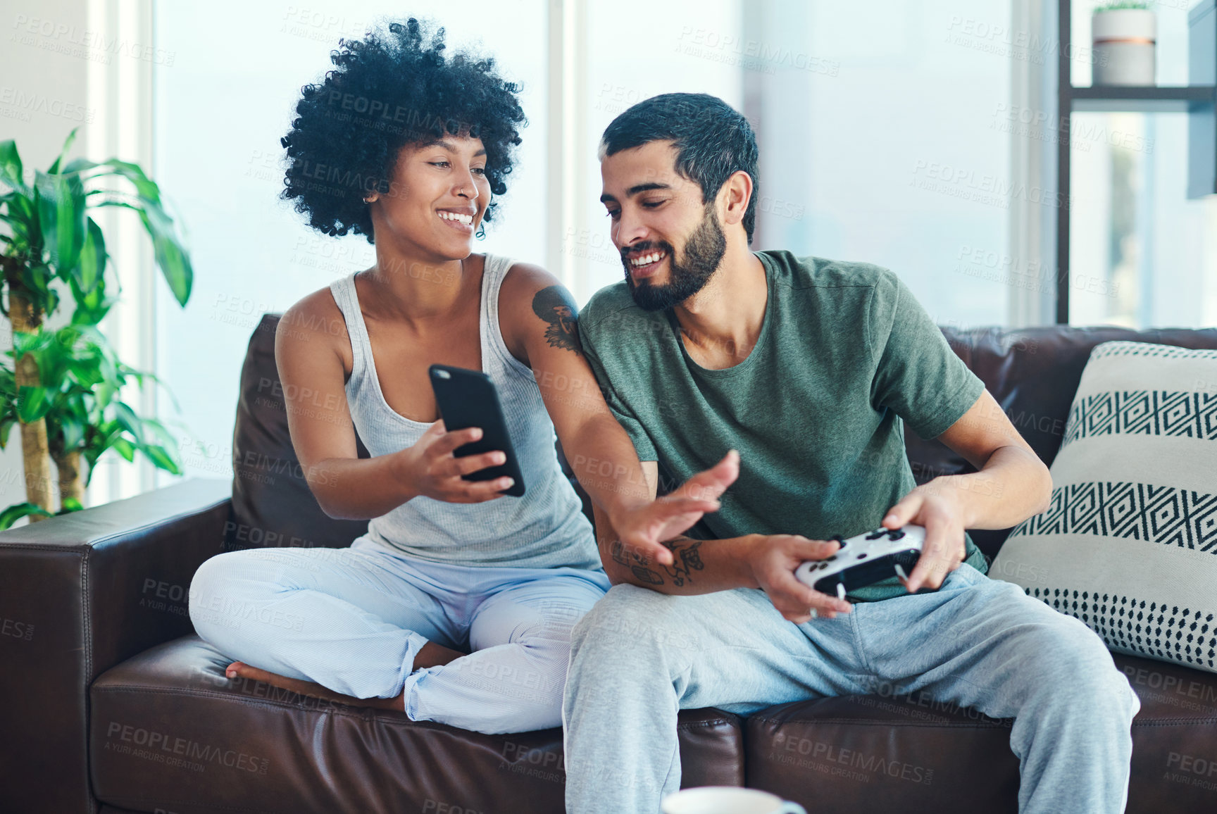 Buy stock photo Shot of a woman showing her boyfriend something on her cellphone while he plays video games