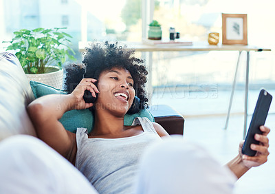 Buy stock photo Shot of a woman using her cellphone while listening to music through headphones at home