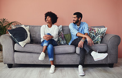 Buy stock photo Shot of a young woman ignoring her boyfriend while sitting together at home