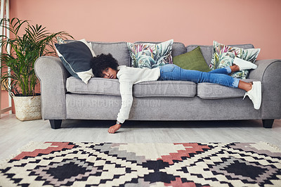 Buy stock photo Shot of a woman looking bored while lying on the sofa at home