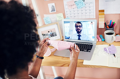 Buy stock photo Shot of a woman holding up a face mask while on a conference call at home