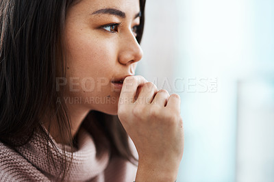 Buy stock photo Shot of a young woman feeling anxious at home