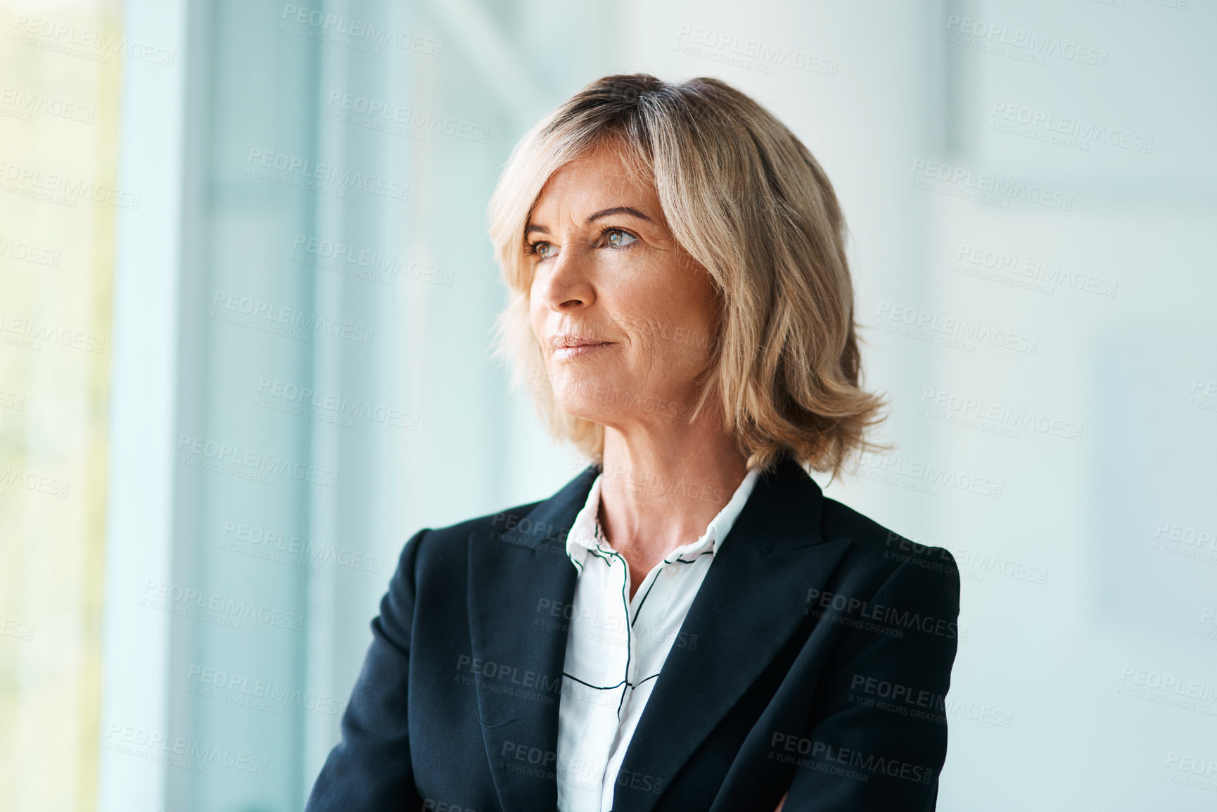 Buy stock photo Shot of a mature psychologist looking out of a window thoughtfully in her office