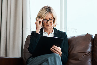Buy stock photo Shot of a mature psychologist sitting on a sofa and writing notes on a clipboard