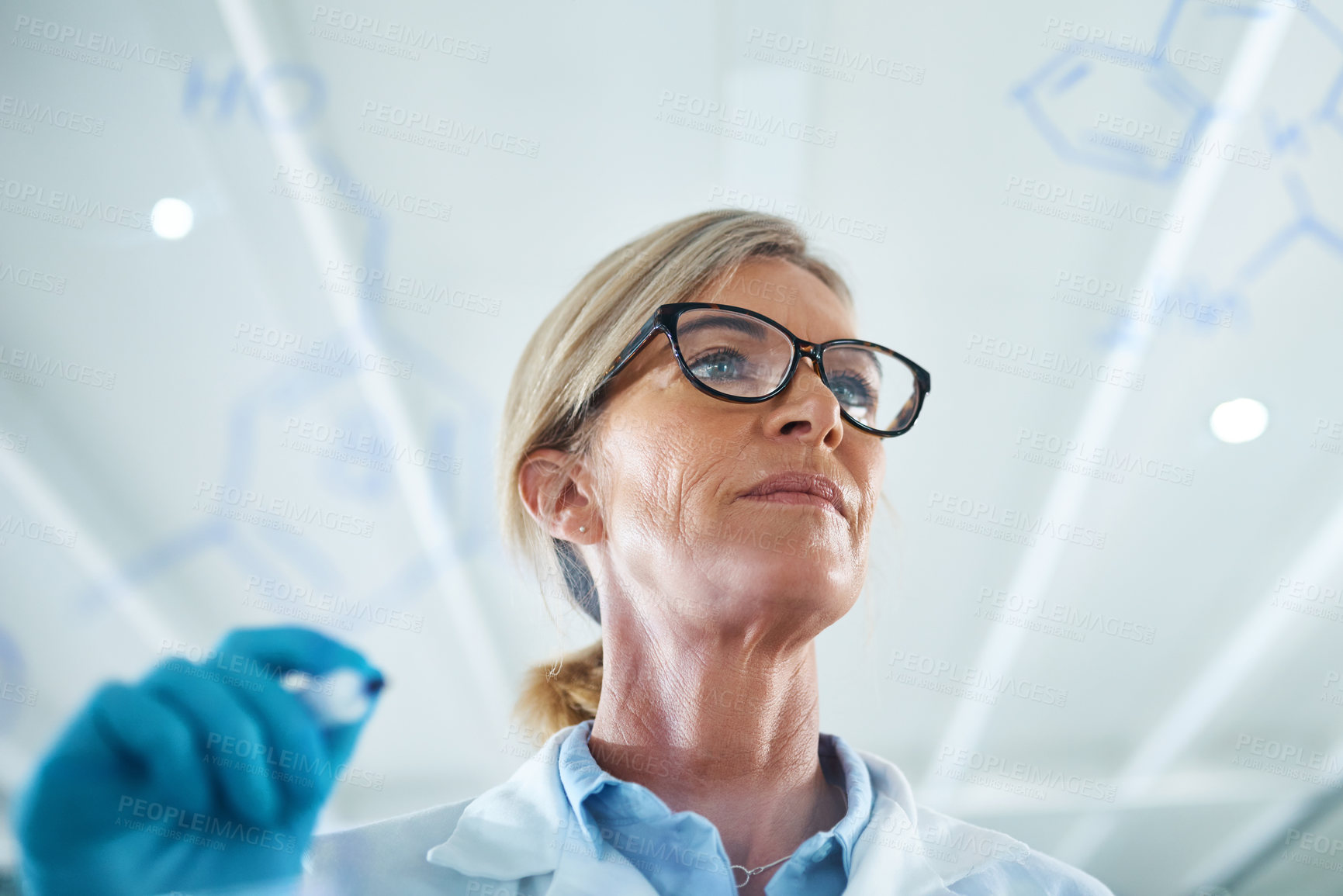 Buy stock photo Shot of a mature scientist drawing molecular structures on a glass wall in a lab