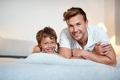 Buy stock photo Shot of a man and his son lying on a bed together
