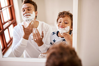 Buy stock photo Shot of a man teaching his young son how to shave at home