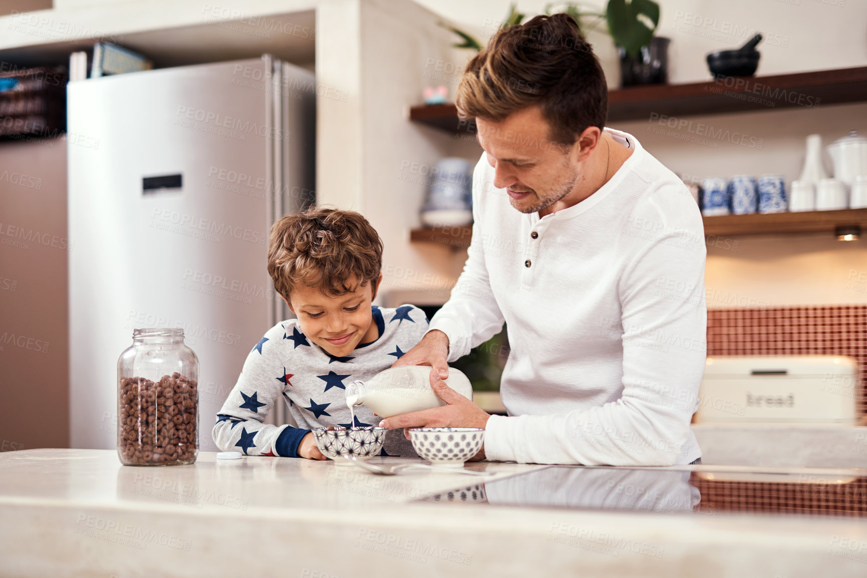 Buy stock photo Shot of a man and his son preparing breakfast at home