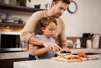 Buy stock photo Shot of a young boy making a sandwich with the help of his father