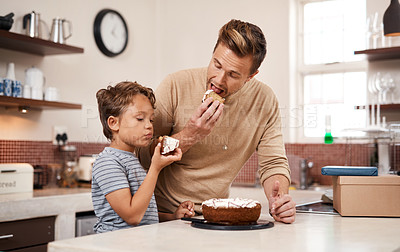 Buy stock photo Shot of a young boy and his father having cake at home