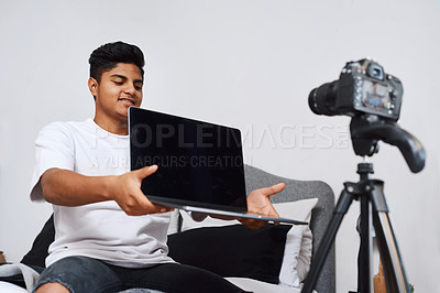 Buy stock photo Cropped shot of a young man using a camera on a tripod to record himself at home