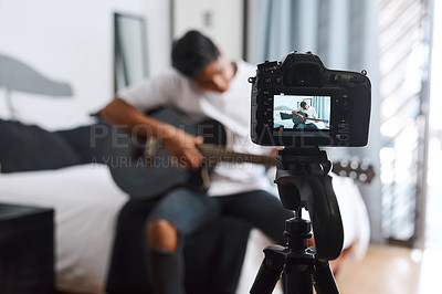 Buy stock photo Shot of a young man recording himself at home while playing the guitar