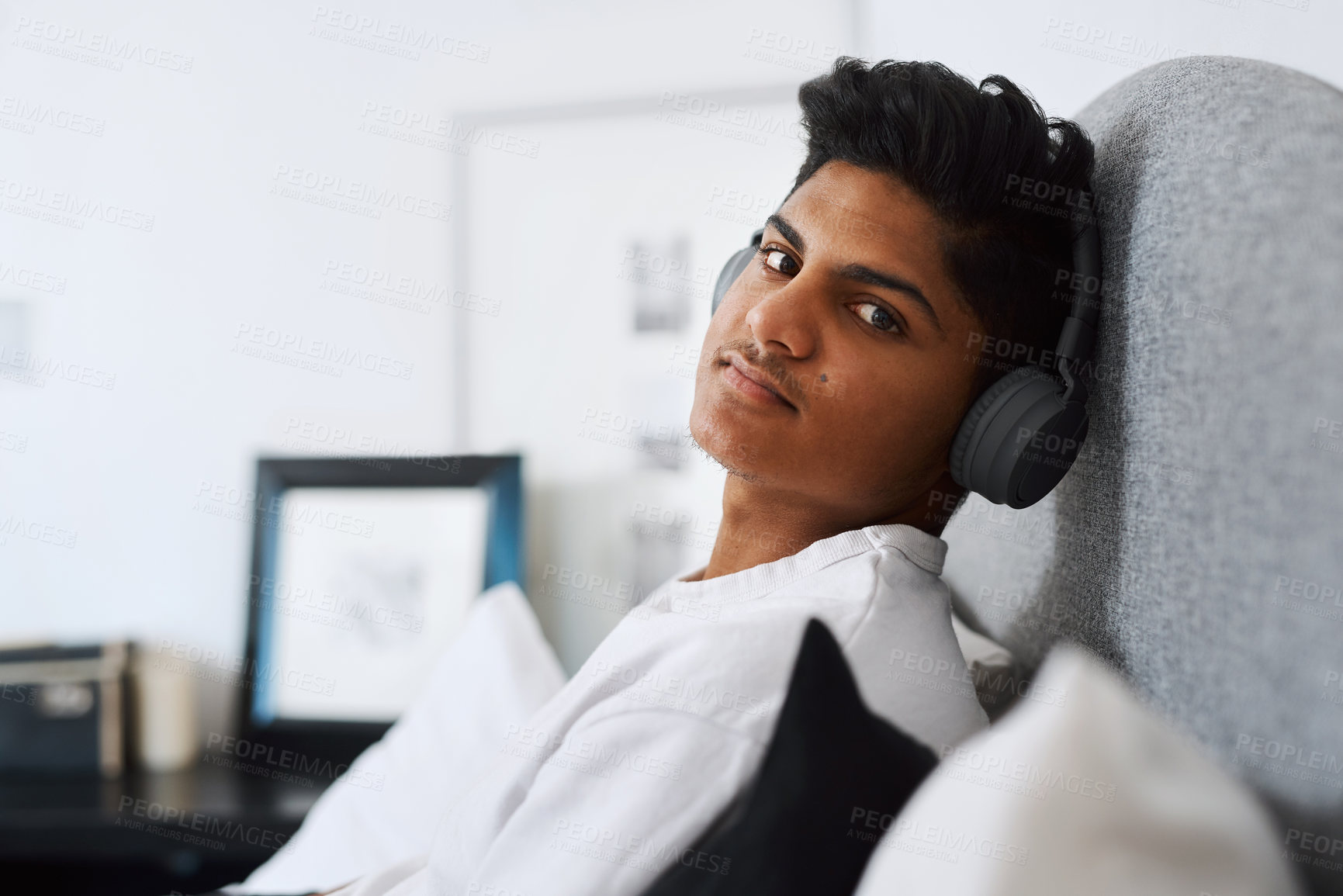 Buy stock photo Cropped shot of a young man listening to music through his headphones while relaxing at home
