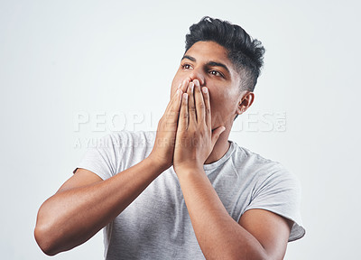 Buy stock photo Studio shot of a young man sitting against a white background