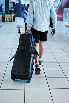 Buy stock photo Cropped shot of a man waking through an airport with his luggage