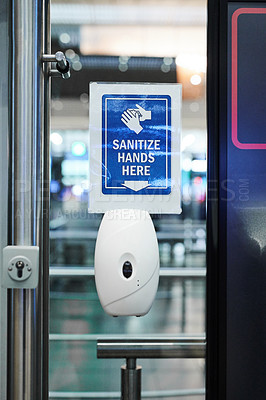 Buy stock photo Shot of an automatic hand sanitiser dispenser on a door in an airport