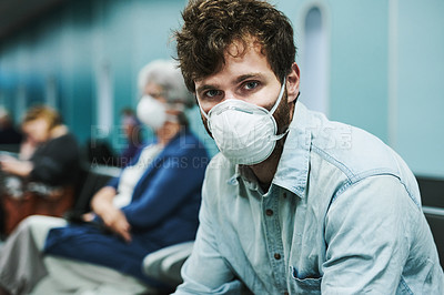 Buy stock photo Shot of a young man wearing a mask and sitting in an airport waiting area