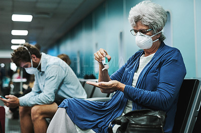 Buy stock photo Shot of a senior woman using hand sanitiser in an airport waiting area