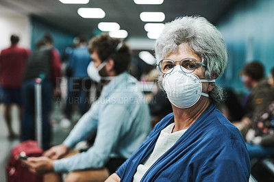 Buy stock photo Shot of a senior woman wearing a mask and sitting in an airport waiting area