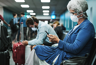Buy stock photo Shot of a senior woman wearing a mask and using a smartphone in an airport waiting area
