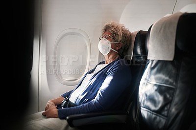 Buy stock photo Shot of a senior woman wearing a mask and closing her eyes while travelling on an airplane