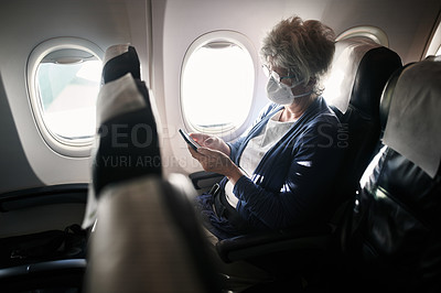 Buy stock photo Shot of a senior woman wearing a mask and using a smartphone in an airplane