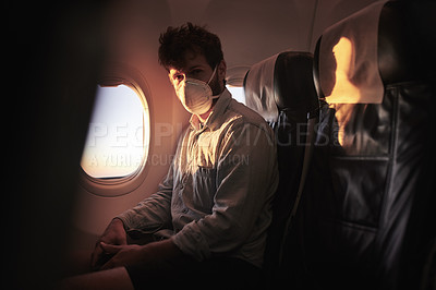 Buy stock photo Shot of a young man wearing a mask while traveling in an airplane
