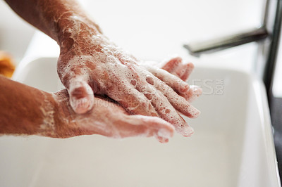 Buy stock photo Shot of an unrecognisable man washing his hands with soap in the bathroom sink at home