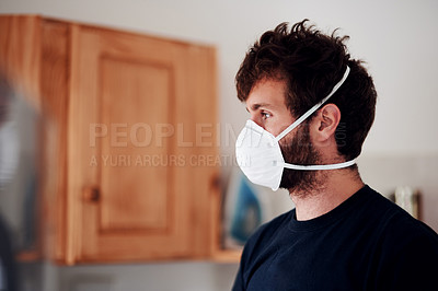 Buy stock photo Shot of a young man wearing a face mask at home