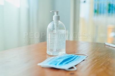 Buy stock photo Shot of a medical mask and bottle of hand sanitiser on a table at home