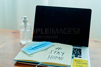 Buy stock photo Shot of a medical mask, hand sanitiser, laptop and notebook saying #STAY HOME on a table at home