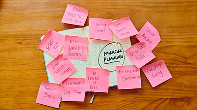 Buy stock photo High angle of a notebook and sticky notes with financial goals written on them on a table at home
