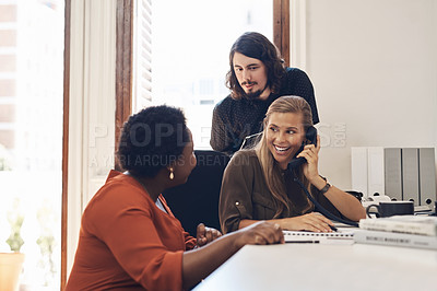 Buy stock photo Shot of a group of businesspeople looking excited while making a telephone call in an office