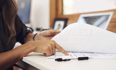 Buy stock photo Closeup shot of an unrecognisable businesswoman going through paperwork in an office
