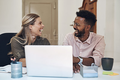 Buy stock photo Shot of two businesspeople laughing while working together in an office