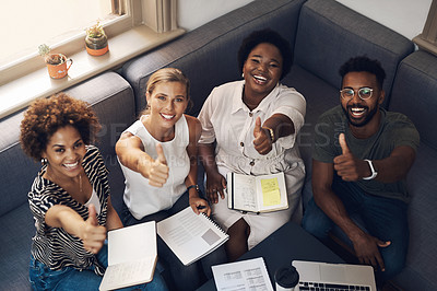 Buy stock photo Shot of a group of young businesspeople showing thumbs up during a meeting in a modern office