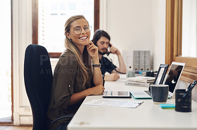 Buy stock photo Portrait of a confident young businesswoman working in an office with her colleague in the background