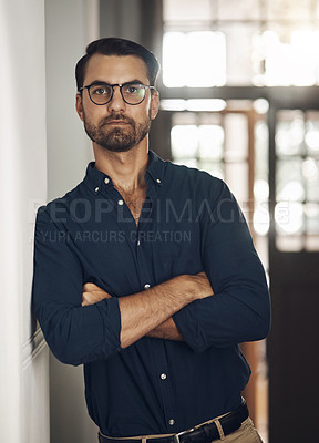 Buy stock photo Portrait of a confident young businessman standing with his arms crossed in an office
