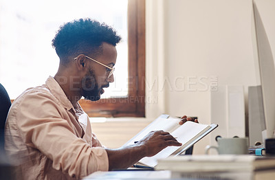 Buy stock photo Shot of a young businessman going through notes from a book while working in an office