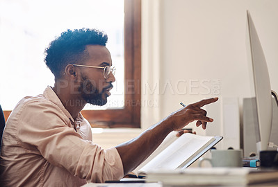 Buy stock photo Shot of a young businessman working on a computer while going through notes from a book in an office