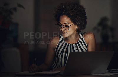 Buy stock photo Shot of a young businesswoman going over paperwork and using a laptop during a late night at work