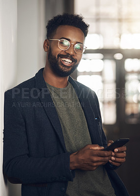 Buy stock photo Portrait of a young businessman using a smartphone in a modern office
