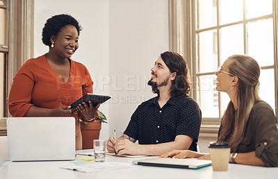 Buy stock photo Shot of a young businesswoman using a digital tablet while having a discussion with her colleagues in an office