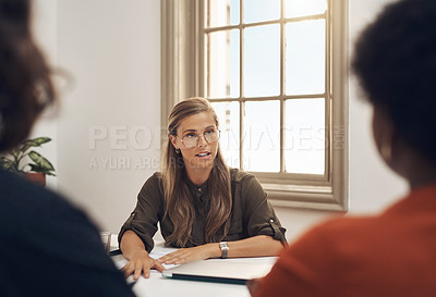 Buy stock photo Shot of a young businesswoman having a discussion with her colleagues in an office