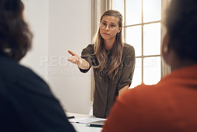 Buy stock photo Shot of a young businesswoman pointing to colleague during a discussion in an office