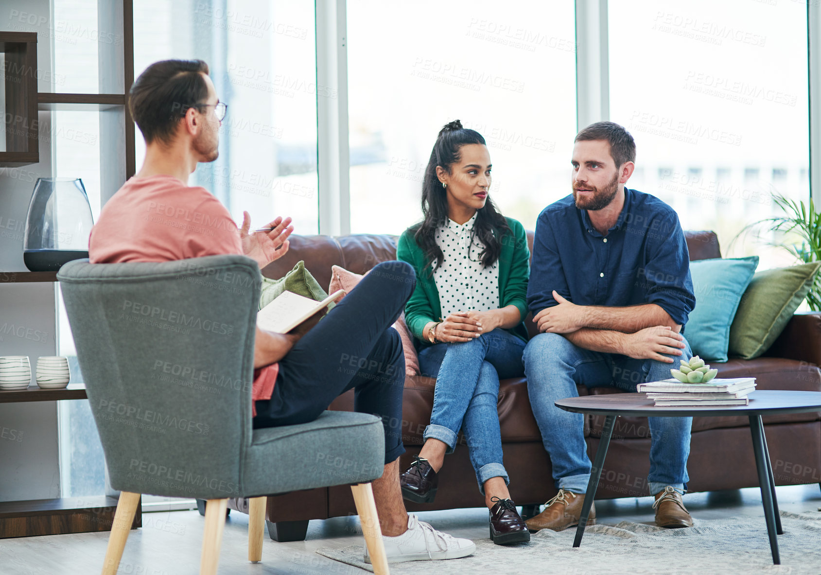 Buy stock photo Shot of two young men and a woman having a discussion in a modern office
