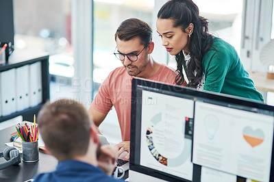 Buy stock photo Shot of a young businessman and businesswoman using a laptop together in a modern office