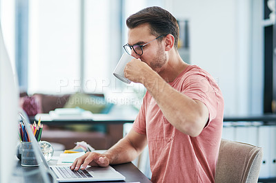 Buy stock photo Shot of a young businessman having coffee while using a computer in a modern office