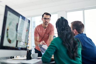 Buy stock photo Shot of a group of young businesspeople having a discussion in a modern office