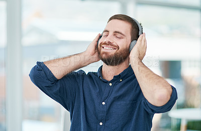 Buy stock photo Shot of a happy young businessman using headphones in a modern office